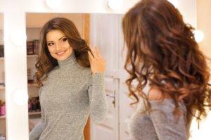 Frau betrachtet ihre Extension im Spiegel